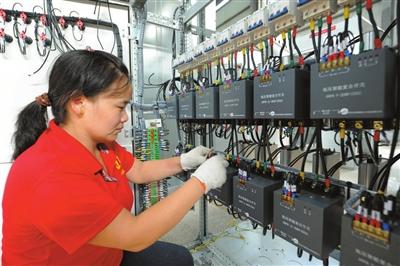 工业园中诚电气有限公司成套组装车间,工人们正忙着对高压计量框接线.